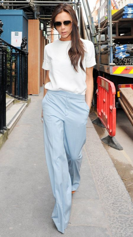 Vittoria Beckham wearing blue pants and cream blouse