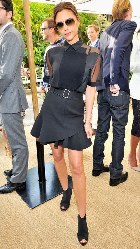 Vittoria Beckham wearing black top and skirt with belt