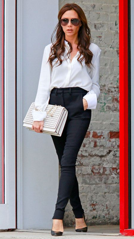 Vittoria Beckham with white button-down and black pants white oversized clutch