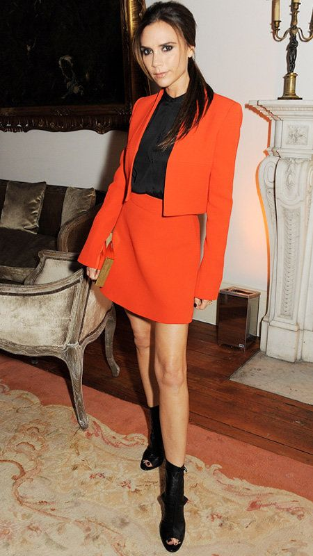Vittoria Beckham in red blazer and mini skirt with black open toe boots